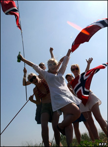 Supporters wave Norwegian flags as the Tour de France pack rides by