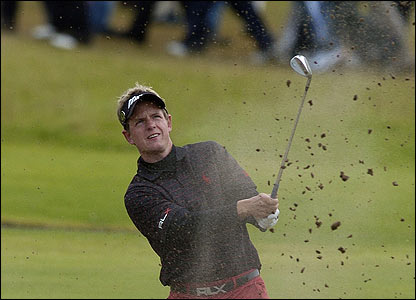 Luke Donald splashes out of the sand at the 18th