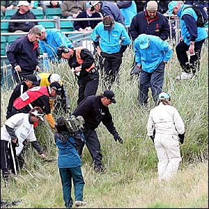 Phil Mickelson (bottom centre) receives help in looking for his ball on the second