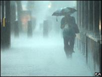 Woman walks through rain in central London