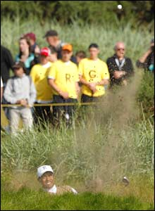 Tiger Woods plays out of the sand on the 9th
