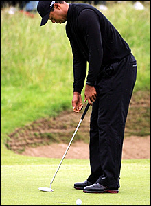 Tiger Woods misses his par putt on the second