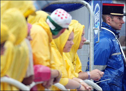Cycling fans wait in the rain 
