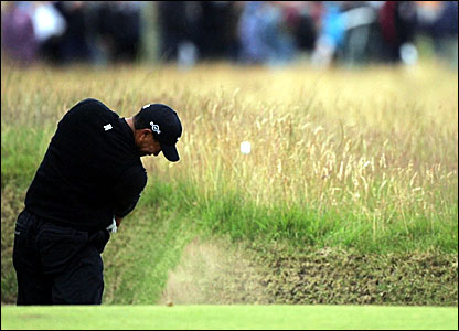 Tiger Woods plays out of a bunker on 10