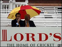 Two MCC members look on as the rain falls at Lord's