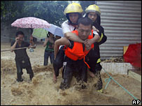 A rescue worker carries a resident through flood waters in Chongqing. File photo