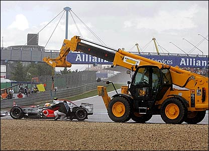 Lewis Hamilton's McLaren is put back on the track by a crane