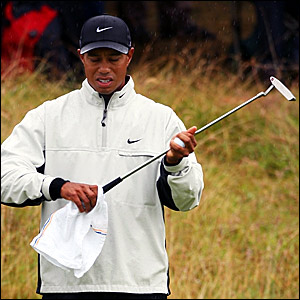 Tiger Woods dries his putter on the first