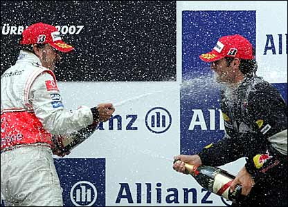 Fernando Alonso (left) sprays Mark Webber with champagne