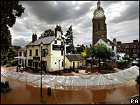 Flood defences hold back the swollen river Severn as it flows past the Plough Inn in Upton on Severn, Worcestershire