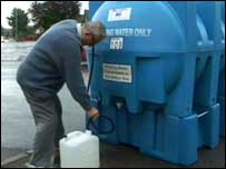 A man collects water from a bowser in Gloucester