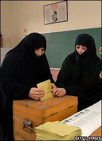سيدتان تدليان بصوتيهما خلال الانتخابات البرلمان المبكرة في تركيا، 22 يوليو/تموز 2007 - ترتديان ملابس سوداء تخفي أغلب الجسم وفي الخلفية صورة مؤسس العلمانية التركية كمال أتاتورك