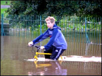 Boy riding through floods