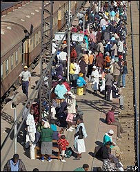 Commuters wait at Harare railway station after commuter buses are impounded for overcharging