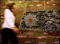A Sotheby's employee (L) walks past a painting by Aboriginal artist Clifford Possum Tjapaltjarri titled Warlugulong 1977, in Sydney, 12 July 2007.