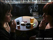 Two women share a drink in a pub