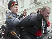 Милиционер задерживает участника демонстрации в Москве