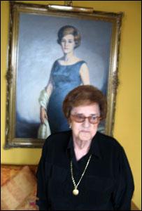 Corín Tellado en su casa delante de un retrato suyo