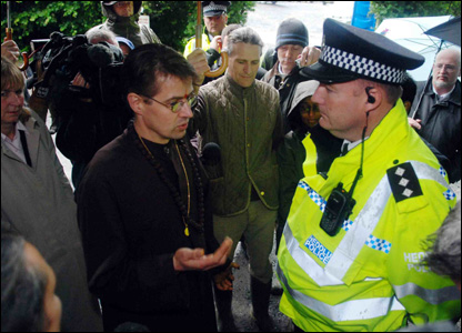 Brother Alex talks to police chief inspector Ian John by the gates of Skanda Vale.