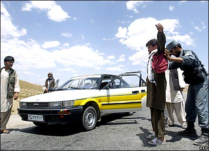 Afghan policemen search a vehicle and its passengers at a checkpoint.