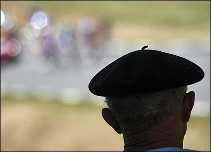 A Frenchman wearing a beret watches the race