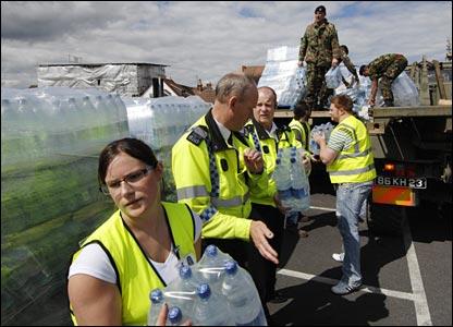 Police, soldiers and volunteers unloading water