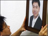 A Korean man hangs a picture of Bae Hyung-kyu, who was killed on Wednesday