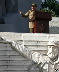 Raul Castro gestures above a carving of his brother, Fidel