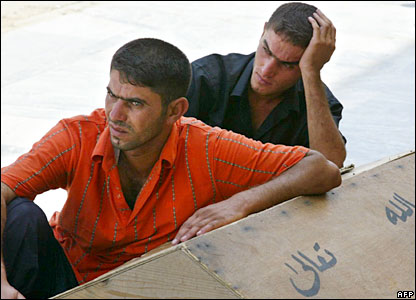Two men lean against the coffin of a slain relative in the Shia holy city of Najaf, Iraq.