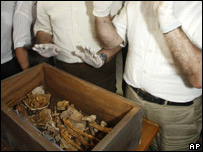 Scientists in front of a box containing the exhumed bones of two 15th century humanists