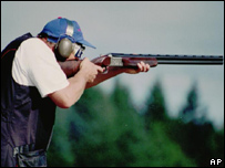 A man aiming a shotgun