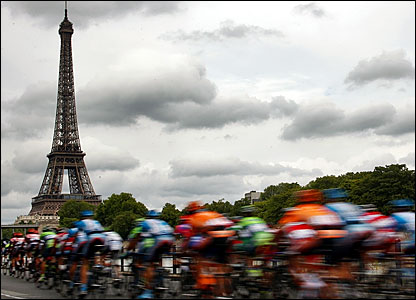 The peloton rides alongside the river Seine with the Eifel Tower in the background