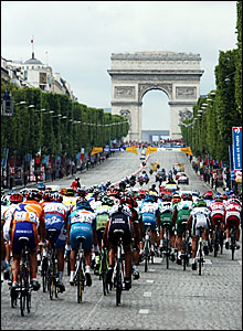 The peloton rides up the Champs-Elysees towards the Arc de Triomphe