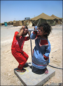 Iraqi refugees drink water at a refugee camp in Najaf