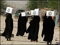 Iraqi women carry humanitarian aid packages in eastern Baghdad