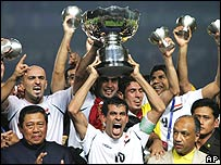 Iraq's Younis Khalef, center, holds up the trophy as he celebrates with teammates after winning Asia Cup soccer final match against Saudi Arabia as Indonesian President Susilo Bambang Yudhoyono, lower