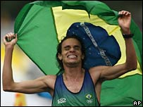 Franck Caldeira of Brazil waves his nation's flag as he wins the men's marathon