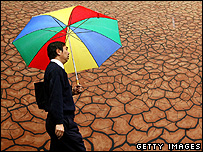 Commuter walking past a mural of a drought (Getty Images)