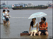 Couple sit on a flooded park bench beside the Yangtze in Wuhan, Hubei province, China - 29/07/07