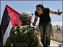Israeli soldier and a Palestinian argue in the West Bank