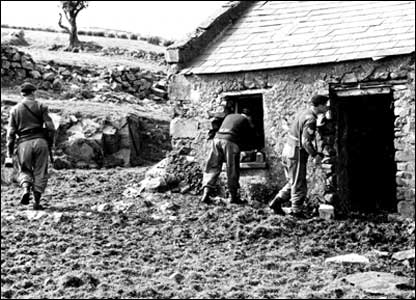 Soldiers search an outbuilding in a remote part of the Northern Ireland countryside