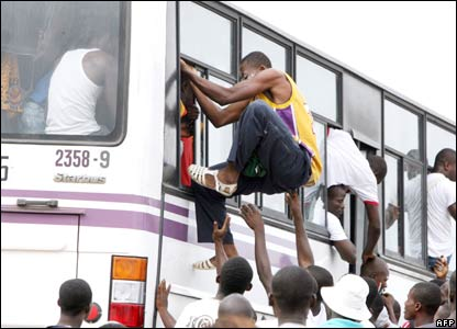 A crowd struggles to board a bus in Abidjan, southern Ivory Coast