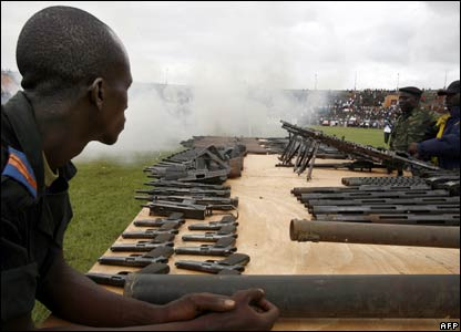 A former rebel fighter surveys a collection of soon-to-be destroyed guns