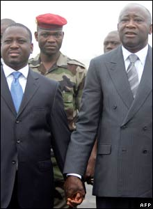 Prime Minister Guillaume Soro (L) and Mr Gbagbo (R) are pictured holding hands at Bouake airport