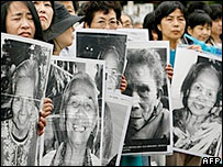 Japanese women hold portraits of former comfort women in front of the Japanese parliament in Tokyo
