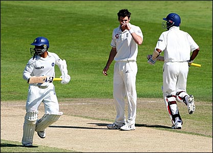 James Anderson (centre) looks on as Dinesh Karthik (left) and Wasim Jaffer run between the wickets