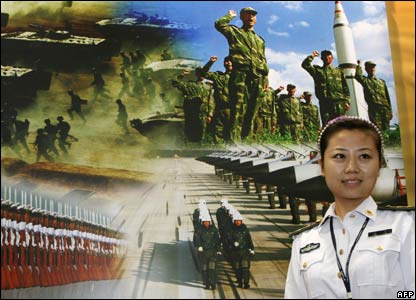 A female PLA soldier stands in front of a recruitment poster at an exhibition in Shanghai