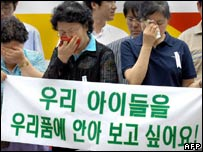 "Relatives of South Koreans kidnapped in Afghanistan cry as they display a banner reading 'We want to hug our kids"" outside at the US embassy in Seoul, 01 August 2007"