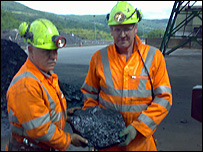 Workers with piece of coal at mine