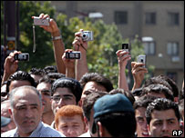 Onlookers use mobile phones and cameras